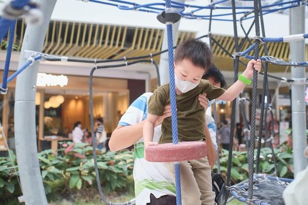 코비드-19 발병 시 아버지와 함께 실내 놀이터에서 빨 수 있는 얼굴 마스크를 쓴 귀여운 아시아 소년 아이가 정글 체육관을 오르고, 새로운 일반 생활 방식 개념 - 선택적 집중