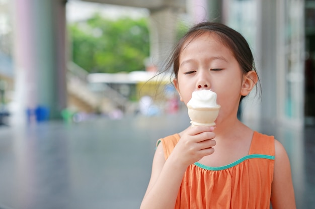 Cute little asian child girl enjoy eating ice cream cone.