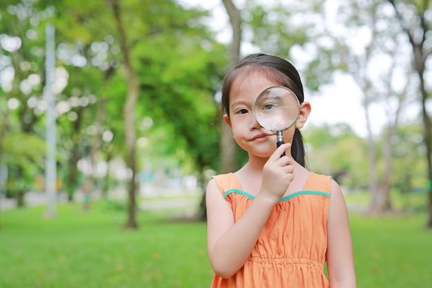 Симпатичная маленькая девочка азиатских детей, глядя через magnifiying стекла на траве на открытом воздухе.