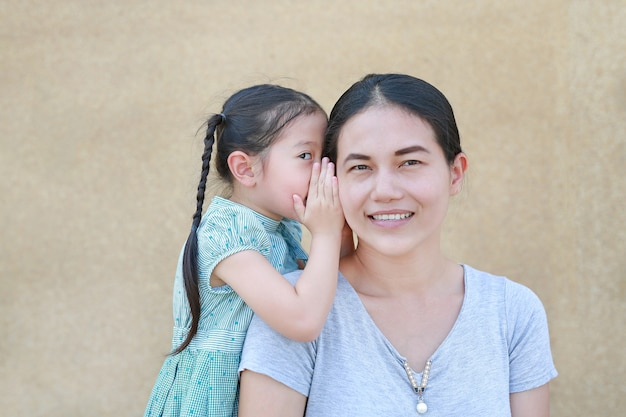 Cute little asian child girl whispering a secret to her young mothers ear at home.