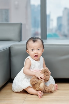 Cute little asian girl in beautiful dress sitting on the floor with teddy bear