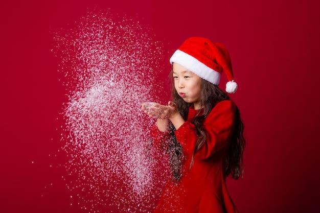 산타 모자를 쓴 귀여운 아시아 소녀가 빨간 배경에 손바닥에서 눈을 날려버린다