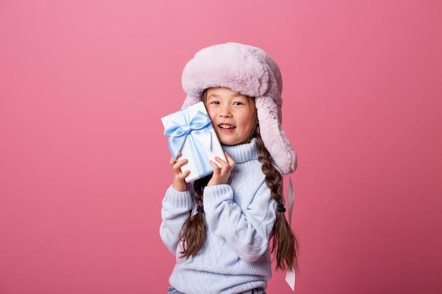 Милая маленькая азиатская девушка в зимней шапке и свитере держит подарочную коробку. рождественская концепция, пространство для текста