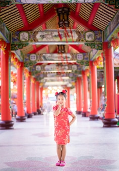 笑顔で寺院に立っている中国の伝統的なドレスでかわいいアジアの女の子。幸せな中国の新年のコンセプトです。