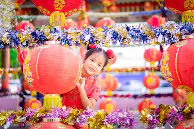 お寺で笑顔の中国の伝統的なドレスでかわいいアジアの女の子。幸せな中国の新年のコンセプトです。