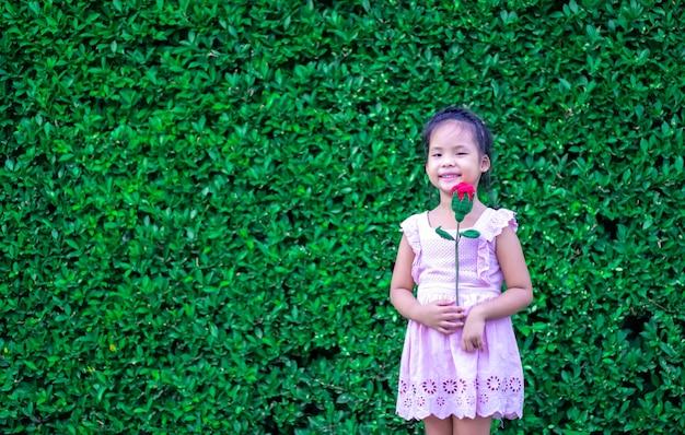 公園で赤いバラを保持しているドレスでかわいいアジアの女の子