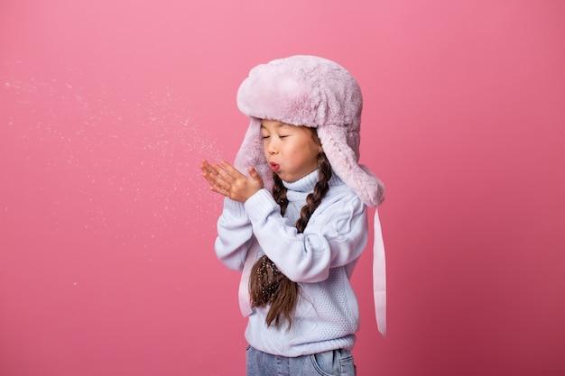 Милая маленькая азиатская девушка в зимней одежде сует снег с пальм. конец зимы, розовый фон, место для текста