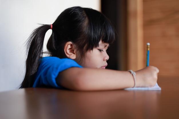 귀여운 아시아 소녀는 테이블에 연필로 책을 쓰고있다
