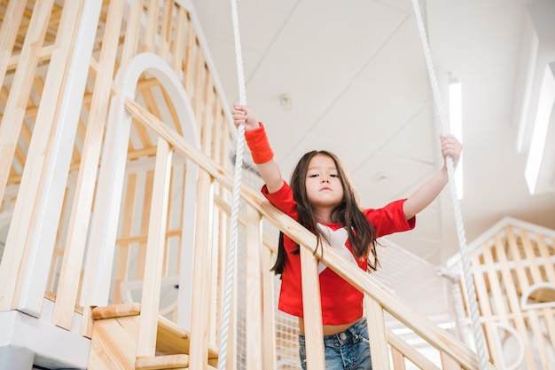 Cute little asian girl looking at you while standing on wooden staircase and holding by ropes on playground