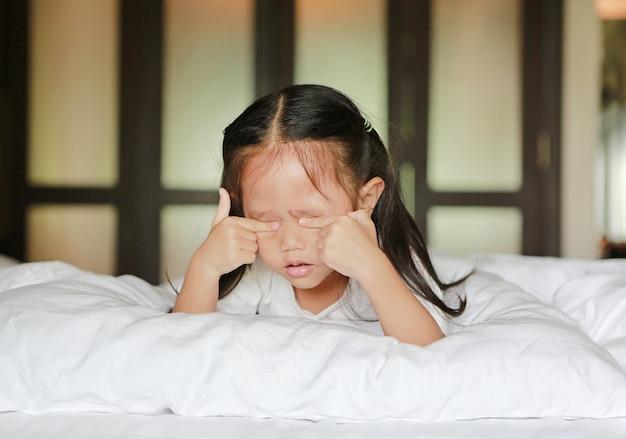 Cute little asian girl in lying on a bed rubs eyes