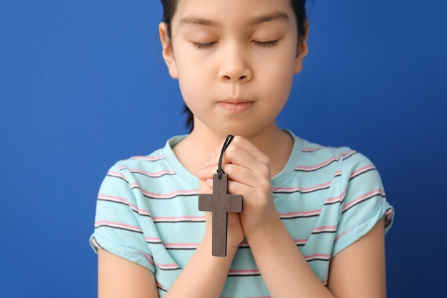 Cute little asian girl praying on color background