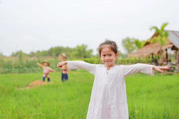 귀여운 아시아 소녀 신선한 녹색 논에서 팔을 스트레칭.