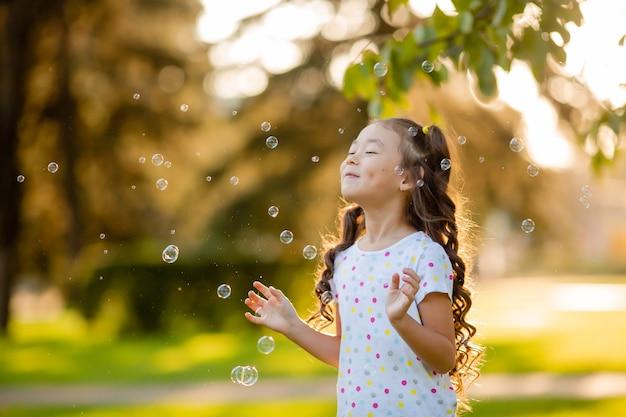 Cute little asian girl in the summer on a walk blowing soap bubbles