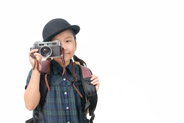 Милая маленькая азиатская девушка фотографирует при винтажная изолированная камера и космос экземпляра