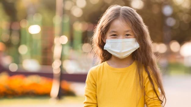 医療マスクを身に着けているかわいいアジアの女の子