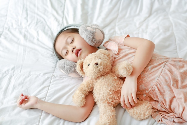 Cute little asian girl wearing winter ear muffs with teddy bear lying on the bed at home