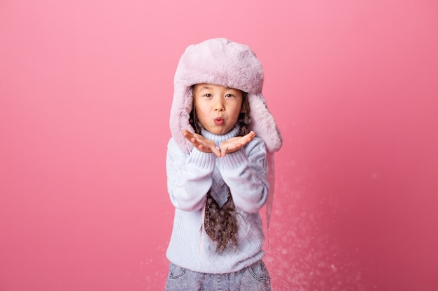 Cute little asian girl in winter clothes blows snow from palms. winter end, pink background, space for text