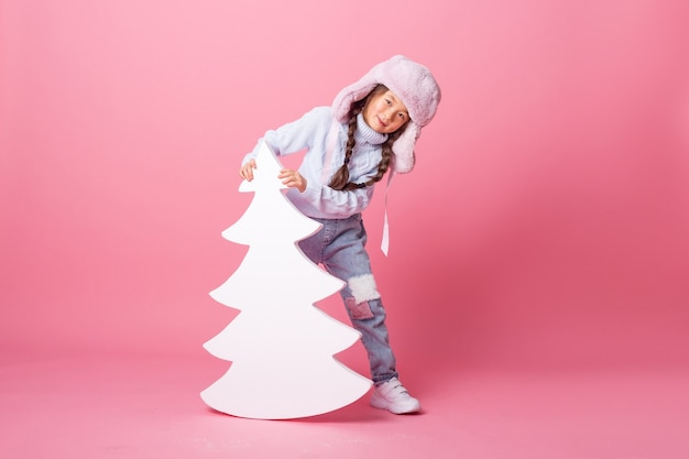 A cute little asian girl in a winter hat stands next to a christmas tree on a pink background. winter concept, space for text