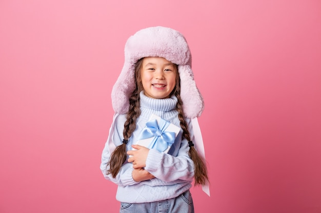Cute little asian girl in a winter hat and sweater holds a gift box. christmas concept, text space