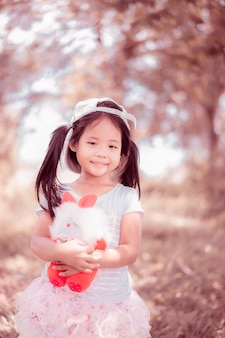 Cute little asian girl with a doll in the park