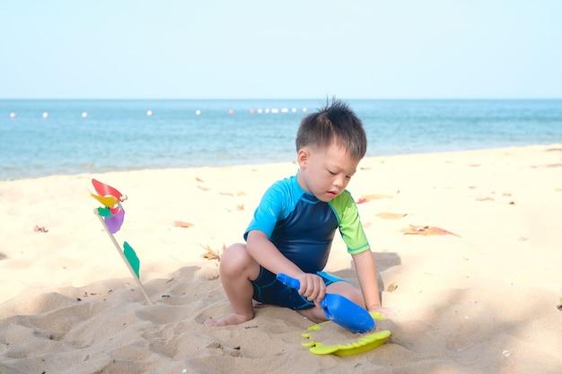 귀여운 작은 아시아 아이, 유치원 소년 앉아서 모래 열 대 해변에서 어린이 해변 장난감 연주