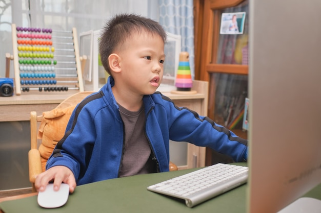 Cute little asian kid with personal computer making video call at home, kindergarten boy concentrate on studying online, attending school via e-learning