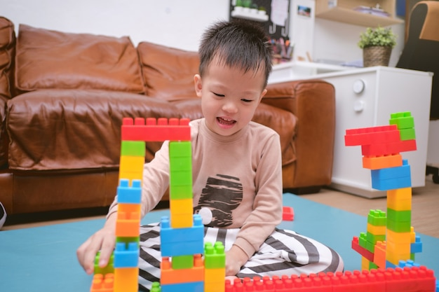 Cute little asian kindergarten boy playing blocks with colorful plastic blocks indoor at home
