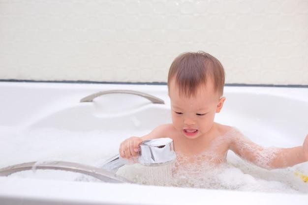 浴槽に座って楽しんでいるかわいい小さなアジアの幼児の男の子の子供