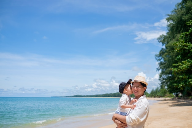 Cute little asian toddler baby boy child kiss dad on white sand beach