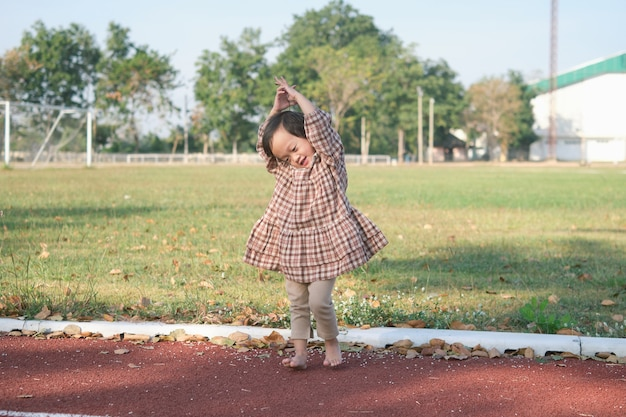 귀여운 아시아 유아 아기 여자 아이 맨발로 트리 포즈 요가 관행 및 여름에 자연에 야외 명상