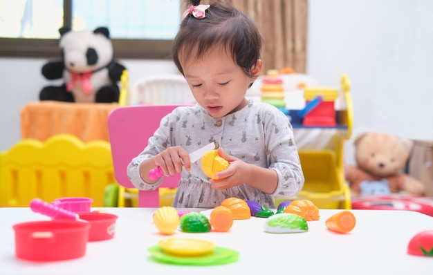 Cute little asian toddler baby girl child having fun playing alone with cooking toys
