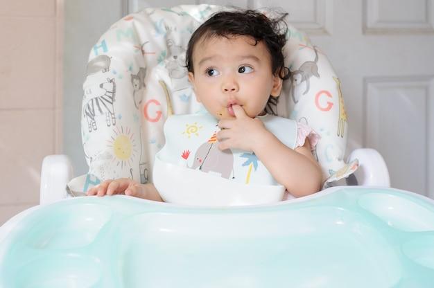 自分の指を吸って赤ちゃんの食卓に座っているかわいい小さなアジアの幼児の女の赤ちゃん。赤ちゃんの表現の概念