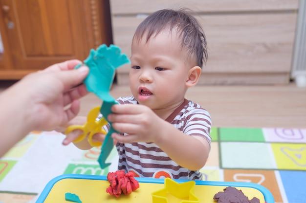 家でカラフルなモデリング粘土遊び生地を楽しんでいるかわいい小さなアジアの幼児の男の子の子供