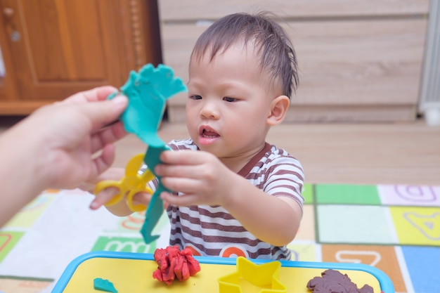 Cute little asian toddler boy child having fun playing colorful modeling clay  play dough at home