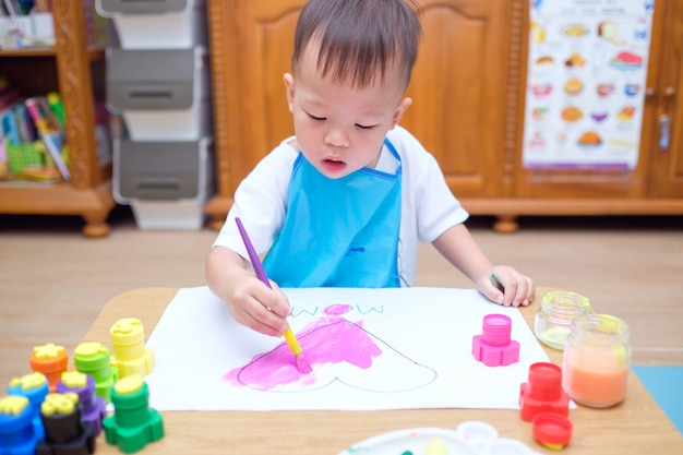 Cute little asian toddler boy child painting with paint brush & watercolors, kid drawing pink heart, making mothers day card
