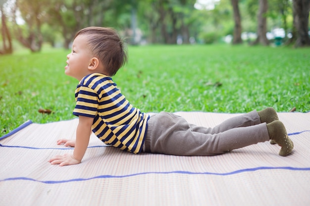 Cute little asian toddler boy child practices yoga in cobra pose and meditating outdoors on nature in summer time, healthy lifestyle concept