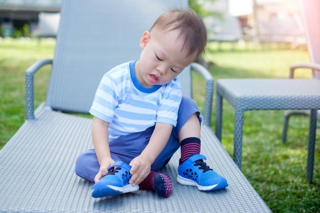かわいい小さなアジアの幼児の男の子の子供が座って、自分の青い靴を履くことに集中します