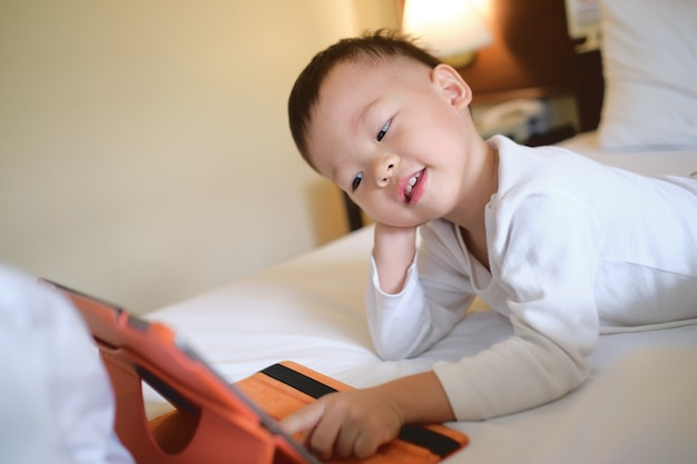 Cute little asian toddler boy child sitting in bed watching a video from tablet pc