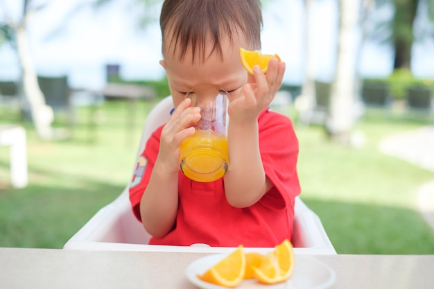 Cute little asian  toddler boy child sitting in high chair holding & drinking tasty orange juice  cold drink in a glass during breakfast