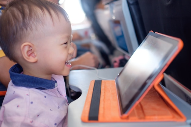Cute little asian toddler boy child using tablet pc watching cartoons during flight on airplane Premium Photo