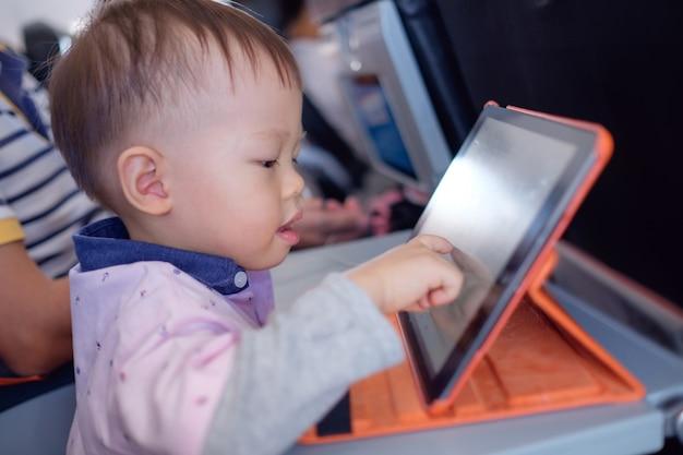 飛行機の飛行中に漫画を見ているタブレットpcを使用してかわいい小さなアジアの幼児の男の子の子供