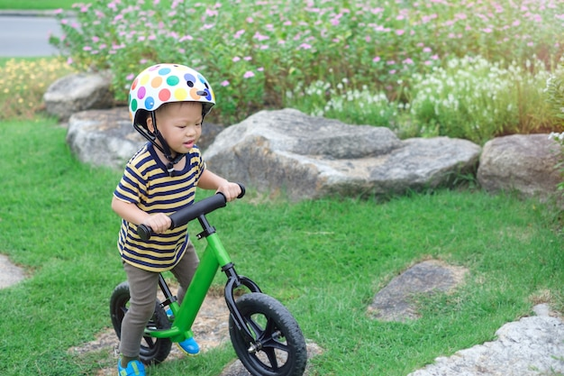 Cute little asian toddler boy child wearing safety helmet learning to ride first balance bike in sunny summer day, kid playing & cycling at park