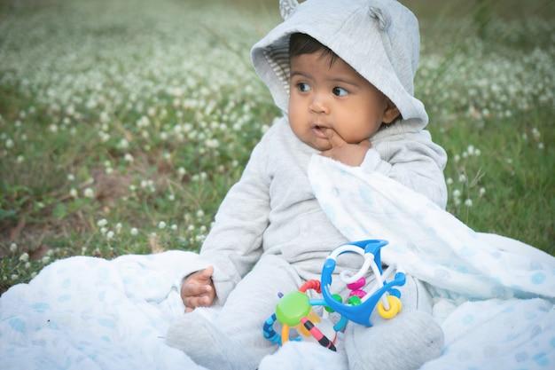Cute little asina baby sitting at white flower garden
