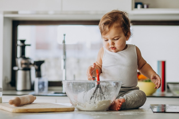 Cute little baby boy cooking at the kitchen