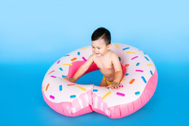 Cute little baby boy in inflated rubber ring