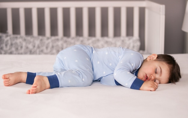 Cute little baby boy in light blue pajamas sleeping peacefully on bed at home.