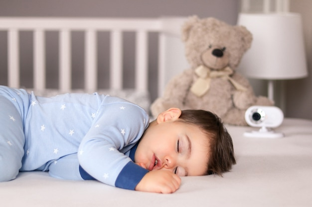 Cute little baby boy in light blue pajamas sleeping peacefully on bed with baby monitor