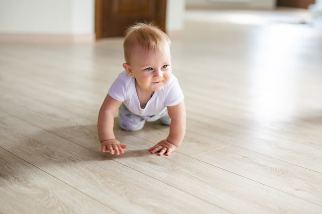 Cute little baby boy lying on hardwood and smiling. child crawling over wooden parquet.