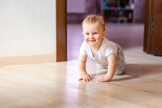 나무에 누워 웃 고 귀여운 작은 아기. 나무 마루 위에 크롤링 하 고 행복 한 얼굴로 찾는 아이. 위에서 봅니다. copyspace.