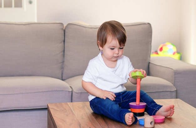 Cute little baby boy playing with colorful wooden pyramid at home.